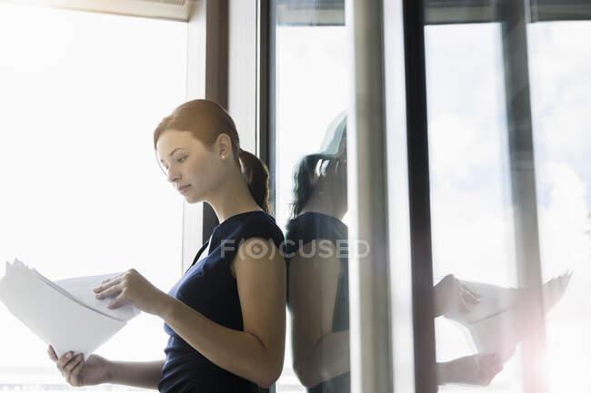 Empresária analisando relatórios em pé à janela no escritório — Fotografia de Stock