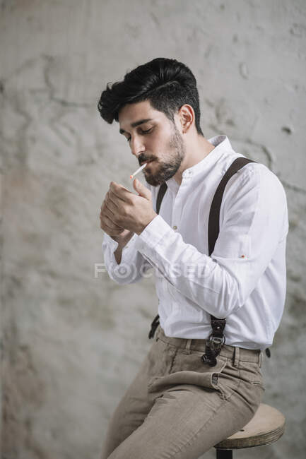 Young man igniting cigarette while sitting on table against wall — Stock Photo
