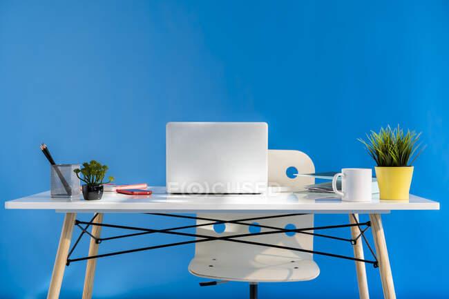 Bureau avec ordinateur portable et mur bleu en arrière-plan — Photo de stock