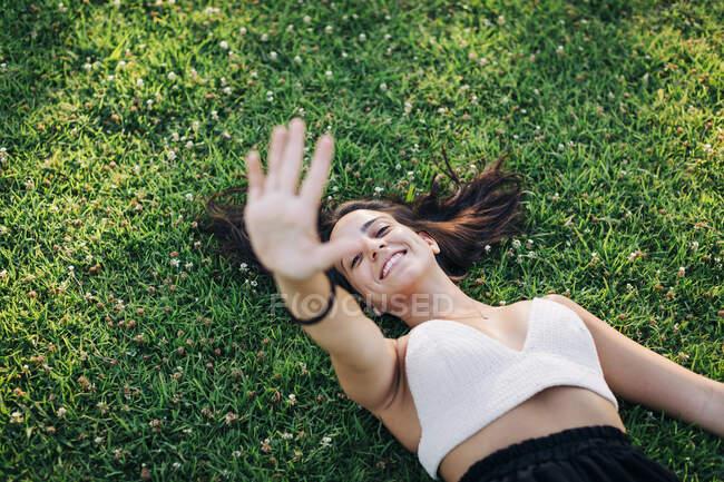 Усміхнена жінка показує, як вона зупиняється, лежачи на траві в парку. — стокове фото