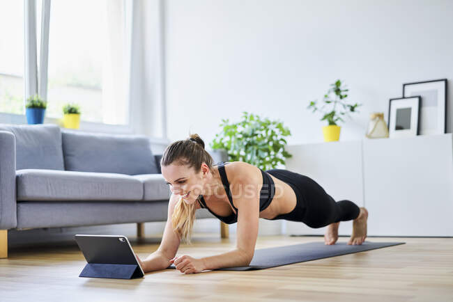 Smiling woman learning plank exercise on internet at home — Stock Photo