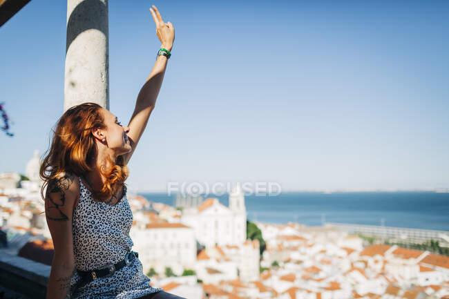 Молодая женщина сидит и жестом знак мира в Alfama, Лиссабон, Португалия — стоковое фото
