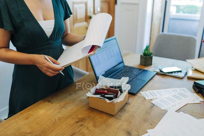 Midsection de position professionnelle féminine avec presse-papiers au bureau — Photo de stock