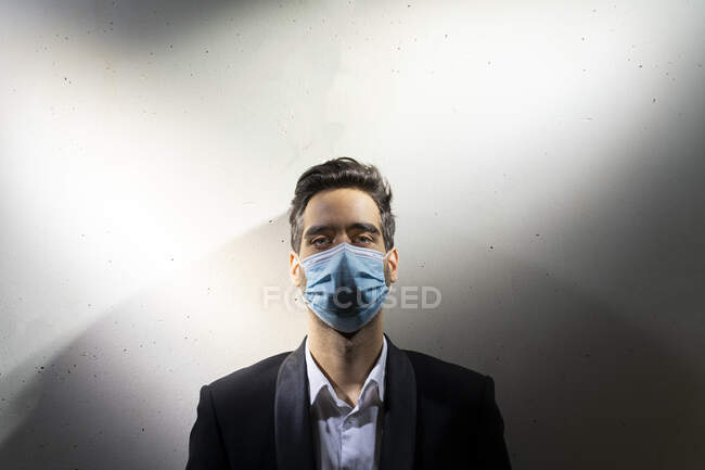 Businessman wearing mask while standing against white wall in office — Stock Photo