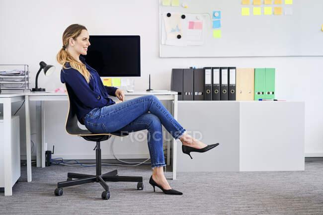 Усміхнена комерсантка сидить на стільці у творчому кабінеті. — стокове фото