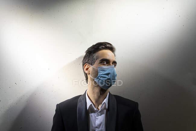 Empresário atencioso usando máscara olhando para longe enquanto estava de pé contra a parede branca — Fotografia de Stock