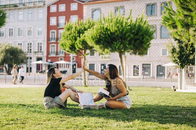 Touristes femmes donnant haute-cinq tout en étant assis sur un terrain herbeux contre la construction dans le parc — Photo de stock