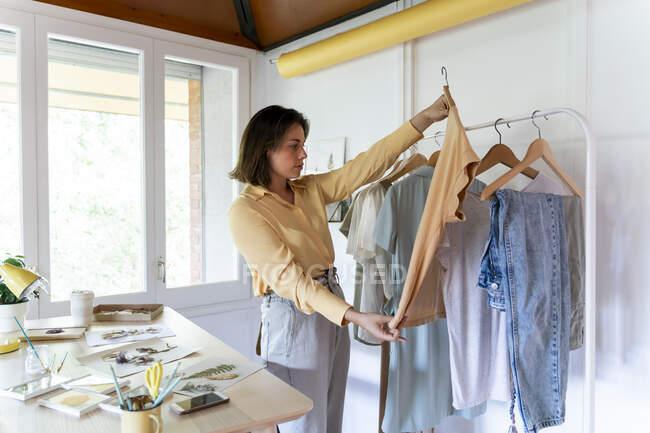 Довірливий молодий дизайнер моди, який оглядає верх, стоячи в магазині. — стокове фото