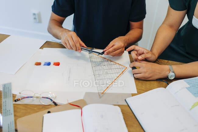Profesionales masculinos y femeninos discutiendo proyecto en escritorio en oficina - foto de stock