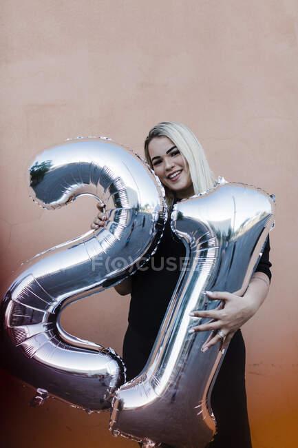 Mujer joven sonriente sosteniendo los globos número 21 mientras está de pie contra la pared - foto de stock