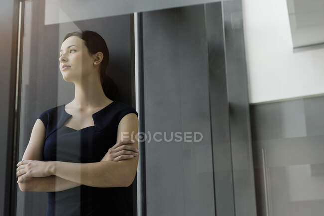 Thoughtful businesswoman with arms crossed standing in office seen through glass door — Stock Photo