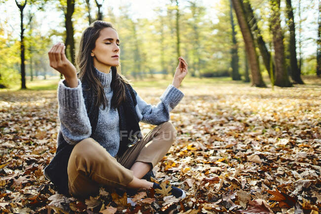 Young woman meditating in autumn forest — Stock Photo