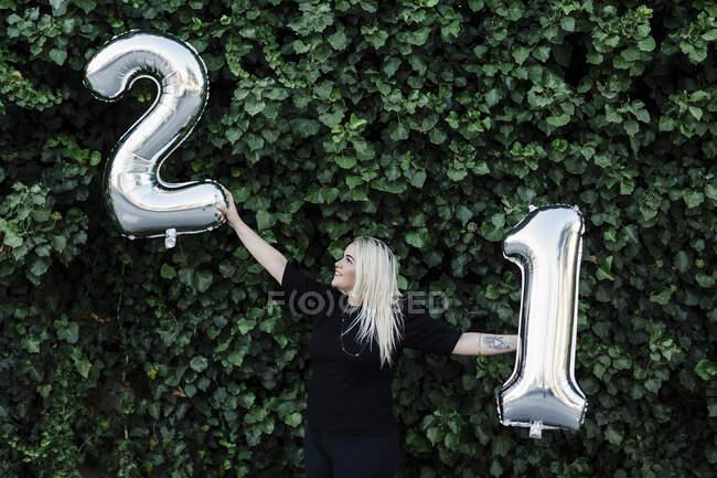 Jeune femme avec les bras tendus tenant numéro 21 ballons contre des plantes dans le parc — Photo de stock