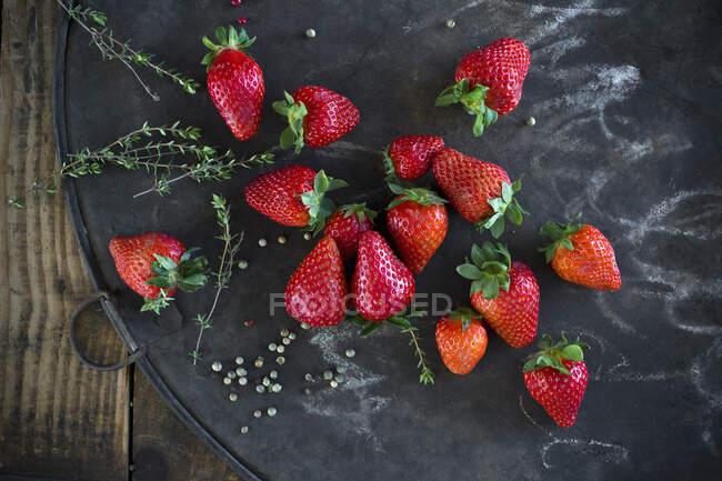 Timo, granturco di pepe e fragole fresche su teglia rustica — Foto stock