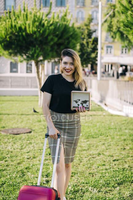 Sorrindo bela mulher com mala segurando caixa enquanto estava em terra gramada no parque — Fotografia de Stock