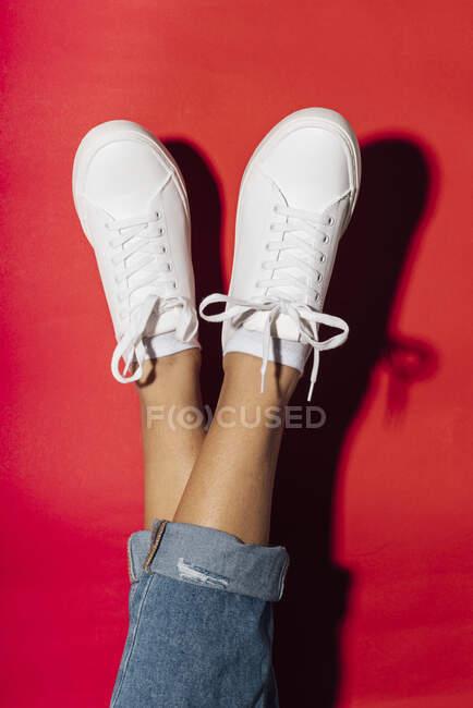 Primer plano de las piernas de la mujer cruzadas y los pies en el fondo rojo - foto de stock