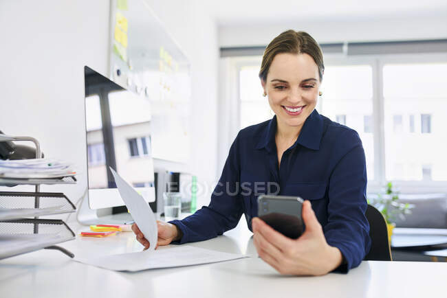 Creative businesswoman using smart phone while doing paperwork in office — Stock Photo