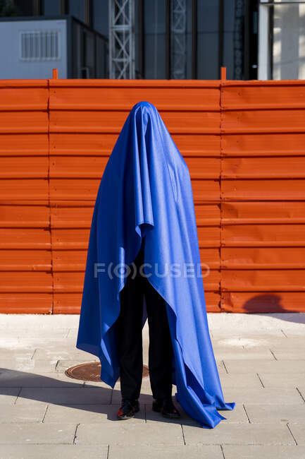 Anonymous man covered by blue cape — Stock Photo