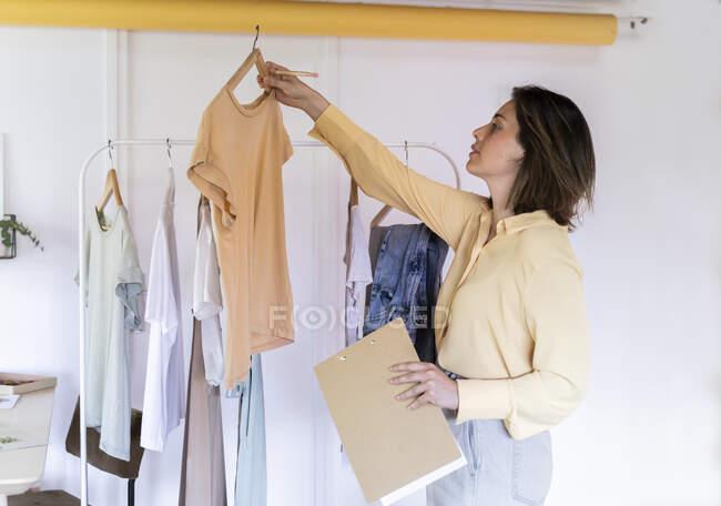 Diseñador de moda seguro de examinar la parte superior, mientras que de pie con portapapeles en la tienda - foto de stock