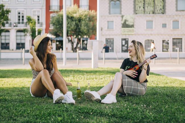 Femme gaie jouant ukulele tout en étant assis avec une amie sur une terre herbeuse — Photo de stock