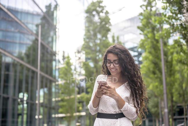 Sorridente giovane donna con i capelli lunghi utilizzando il telefono cellulare mentre in piedi in città — Foto stock