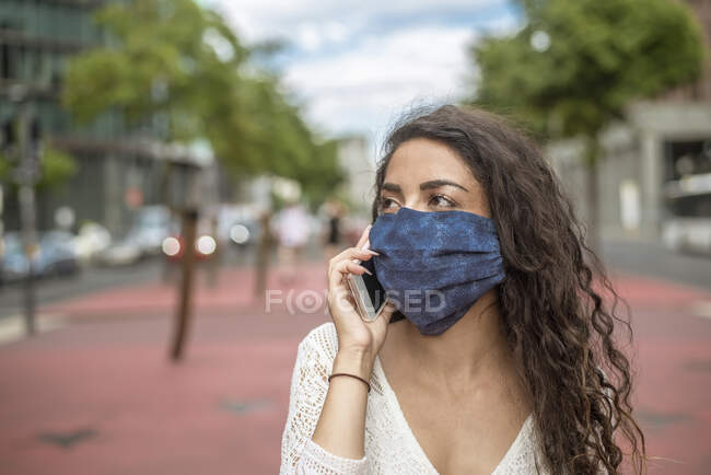 Close-up of young woman wearing mask talking over mobile phone in city — Stock Photo
