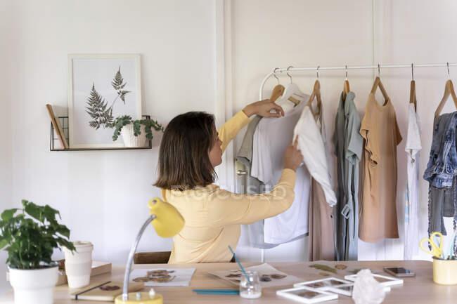 Joven diseñadora de moda femenina mirando ropa colgando de un estante en la tienda - foto de stock