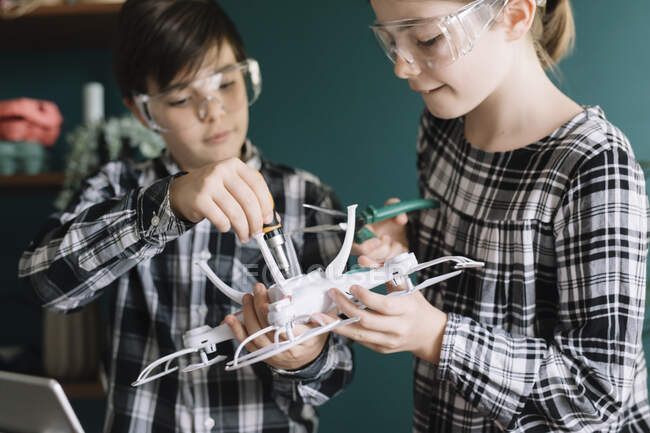 Close-up of siblings making drone at home — Stock Photo