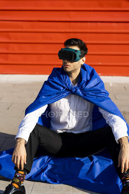 Businessman wearing superhero cape and VR goggles sitting on curb — Stock Photo