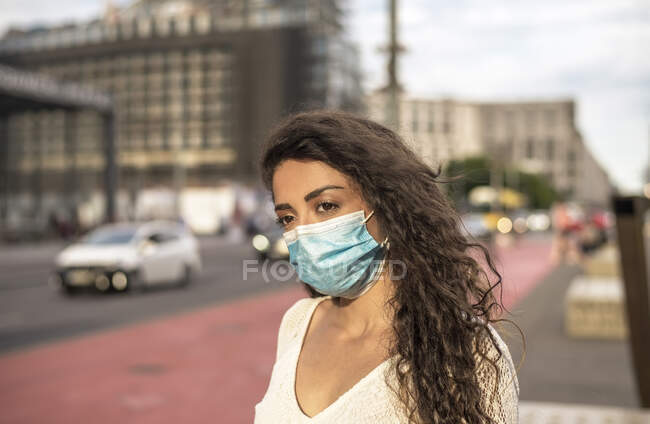 Young woman wearing mask looking away while standing on footpath in city — Stock Photo