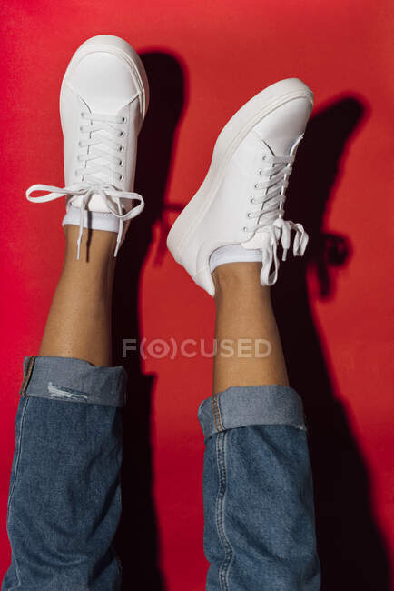 Woman with feet up wearing white sneakers against red background — Stock Photo