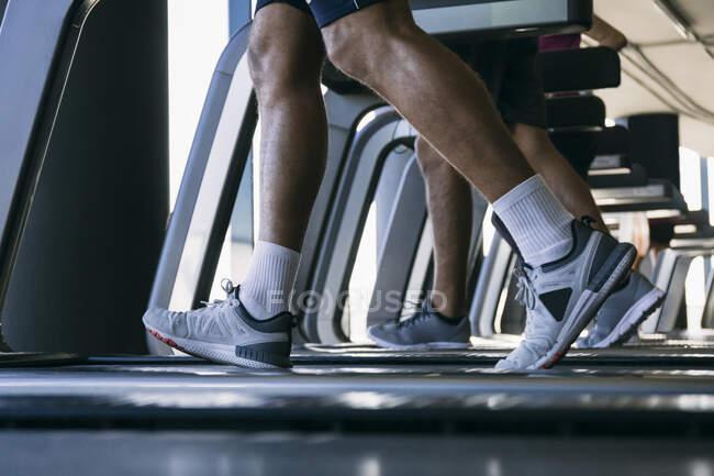 Legs of athletes running on treadmills in health club — Stock Photo