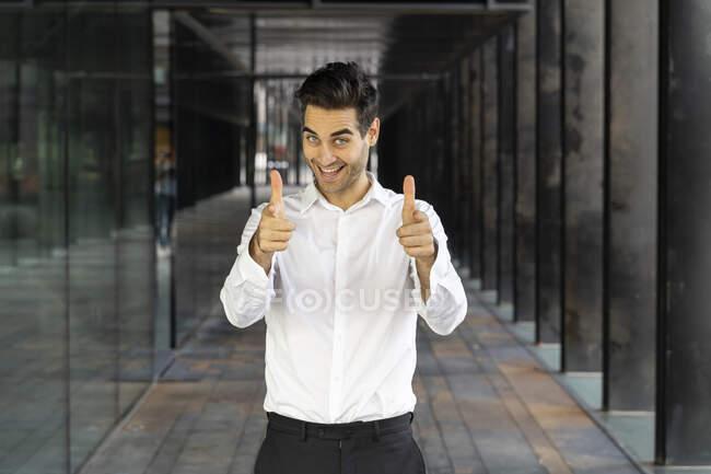 Hombre de negocios sonriente mostrando los pulgares hacia arriba mientras está de pie en la oficina - foto de stock