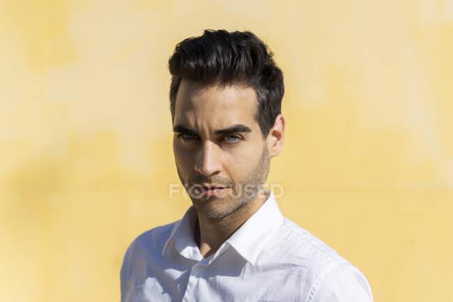 Ritratto di bell'uomo d'affari contro la parete gialla — Foto stock