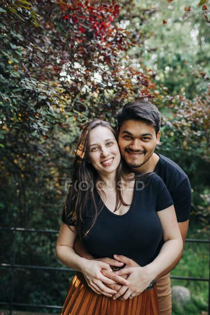 Улыбающийся молодой человек обнимает женщину сзади, проводя выходные в парке — стоковое фото