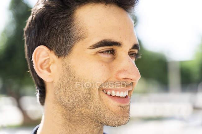 Усміхнена людина дивиться у місто в сонячний день. — стокове фото