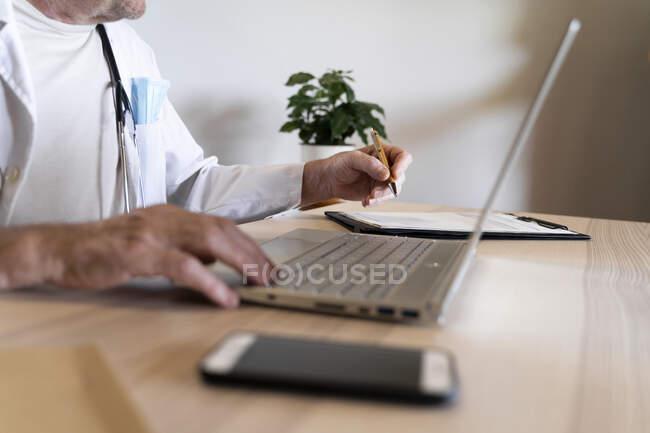 Врач, сидящий за столом в клинике — стоковое фото