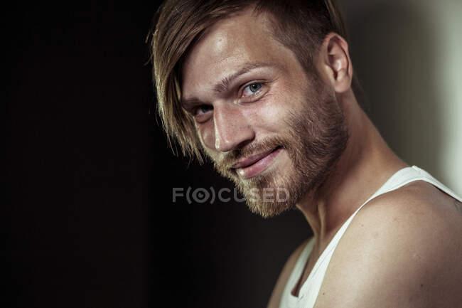 Primer plano del guapo barbudo sonriente contra la pared - foto de stock