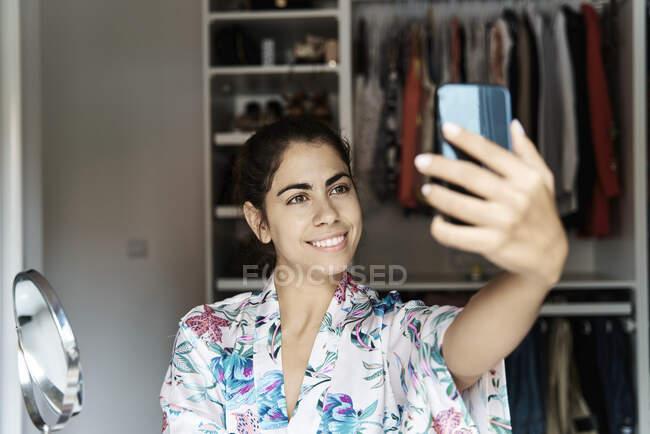 Sorrindo mulher tomando selfie no telefone inteligente em casa — Fotografia de Stock