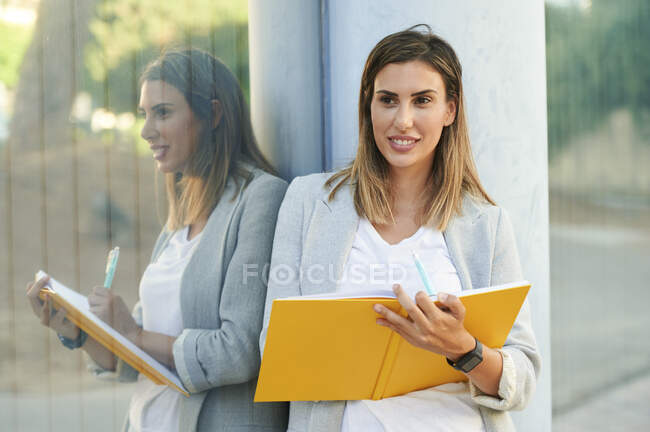 Smiling businesswoman with diary reflecting on window glass — Stock Photo