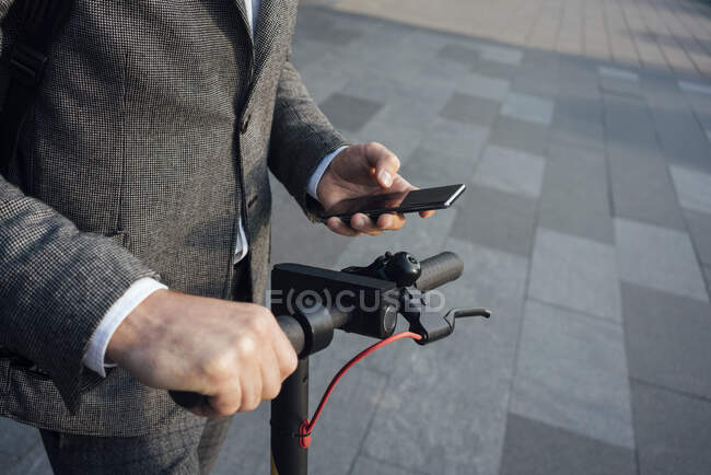 Midsection of male commuter using smart phone while holding electric push scooter handle — Stock Photo