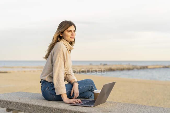 Nachdenkliche junge Frau schaut weg, während sie mit Laptop auf Bank am Strand gegen den Himmel während des Sonnenuntergangs sitzt — Stockfoto