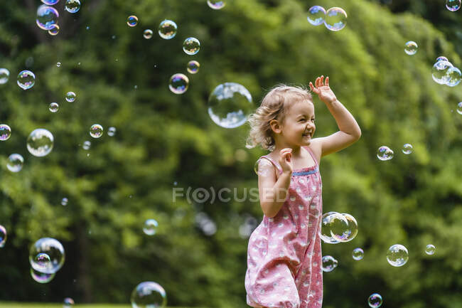 Cheerful girl running amidst bubbles at park — Stock Photo