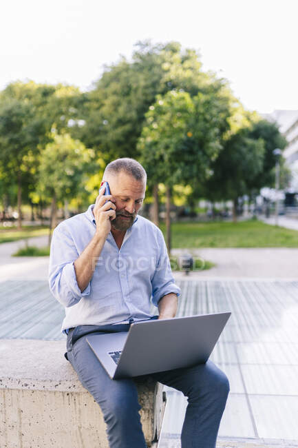 Businessman talking on smart phone while using laptop in office park — Stock Photo