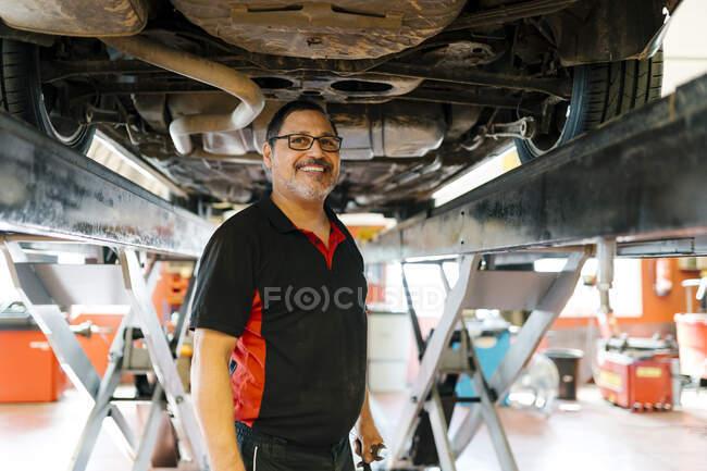 Sorrindo mecânico masculino em pé abaixo do carro na oficina de reparação de automóveis — Fotografia de Stock