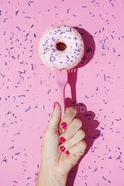 Рука женщины, держащей вилку со сладким пончиком, покрытым сахарной крошкой — стоковое фото
