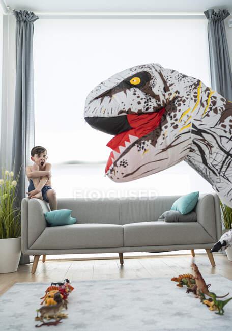 Мальчик без рубашки кричит, глядя на большого игрушечного динозавра в гостиной — стоковое фото