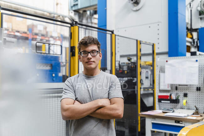 Young male worker with arms crossed at illuminated factory — Stock Photo