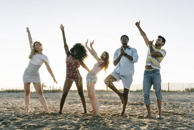 Friends enjoying while doing hand gestures standing on beach — Stock Photo