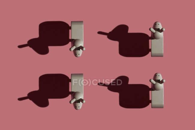 Estudio de cuatro figuritas de burro sobre fondo rojo pastel - foto de stock